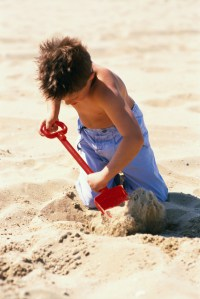 Boy with a spade on the beach